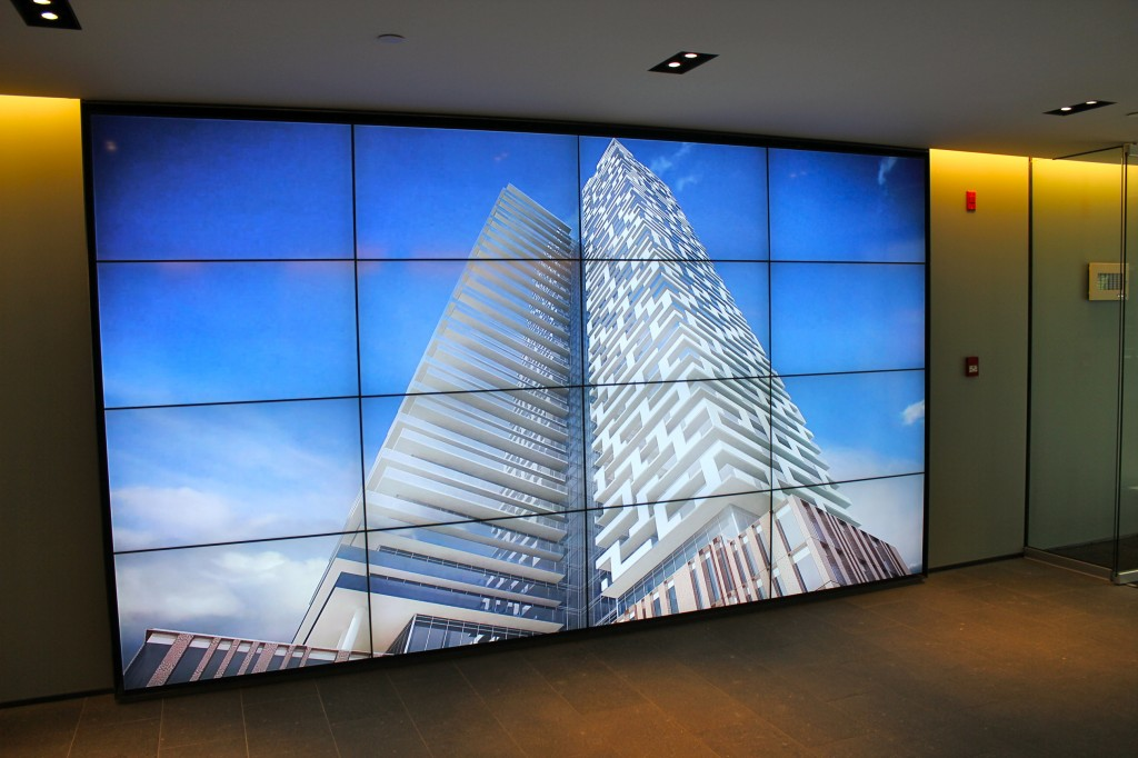 A large screen shows lifelike images of what the completed development will feature.