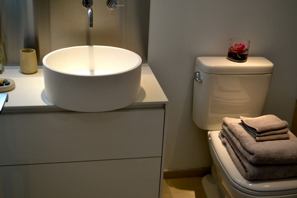All bathrooms have a white Corian sink with a solid core vaneer slab bathroom cabinet, and a vanity mirror with integrated lighting.