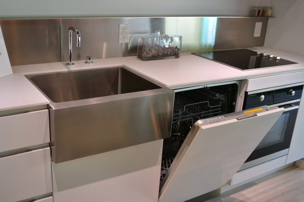 Fully integrated appliances and stainless steel sink and backsplash.