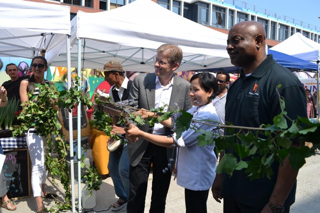 Daniels Vp Martin Blake, aspiring pastry chef Mary-Ann Kalalang, and Toronto Community Housing President and CEO Eugene Jones Jr, cut the ceremonial vine.
