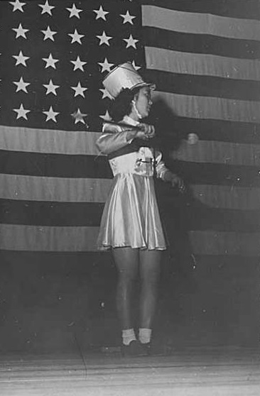 Baton twirler in front of American flag